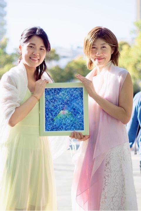 松井守男画伯作 マザーアース「愛の誕生」の絵を持つ二人の女性
