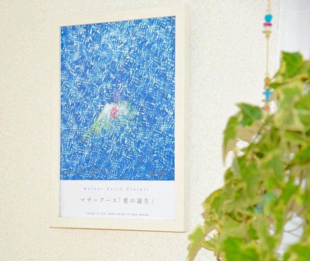 壁にかけられている松井守男画伯作 マザーアース「愛の誕生」の絵